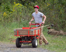 SD student pushing string trimmer in garden cart